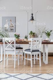 gemusterten teppich und poster in weiß esszimmer interieur mit stühlen am holztisch echtes foto stockfoto und mehr bilder blume