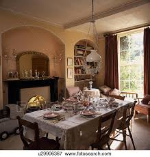 Victorian Glass And Brass Light Above Table With Place Settings On White Cloth In Dining Room Fireplace Alcove