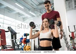 Waist Up Portrait Of Beautiful Young Woman Exercising With Dumbbells Sitting On Bench Helped By Personal