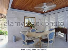 Ceiling Fan Above Cream Table And Traditional Blue Upholstered Chairs In Modern Caribbean Dining Room With