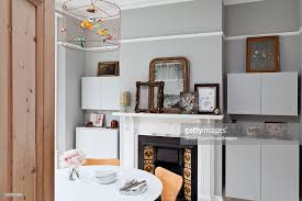 Modern Cupboards Either Side Of Victorian Fireplace In Dining Room Hove Stock Photo