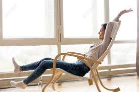 Carefree Young Woman Relaxing On Comfortable Wooden Rocking Chair..