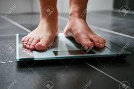 weibliche nackte füße mit waage im badezimmer