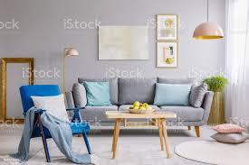 blauer sessel mit kissen und decke stehen auf dem teppich in grau wohnzimmer interieur mit frischen äpfeln am couchtisch aus holz lounge mit kissen