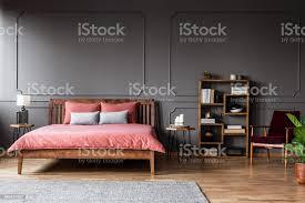 echtes foto einem geräumigen schlafzimmer innenraum mit rosa bett stehend gegen schwarze wand mit formteil neben einer kreativen bücherregal und