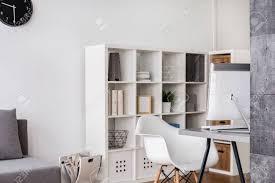 helle ecke eines wohnzimmers mit computer schreibtisch stuhl und große weiße rack