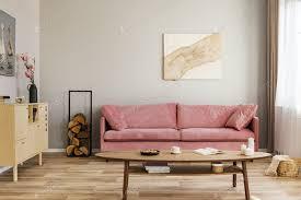 pastell abstrakte malerei auf beige wand hinter samt rosa sofa im einfachen wohnzimmer foto bialasiewicz auf envato elements