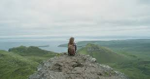 Independent Woman Traveller Sitting At Edge Of Cliff Looking Out Over Ocean Hipster Hiker Girl Relaxing