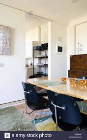 Black Chairs At Wooden Table In Modern Dining Room With Sliding Doors Giving View To Kitchen