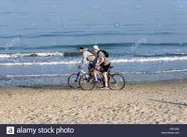 Two Young Lads Riding Bikes On The Beach At Studland Bay Dorset UK