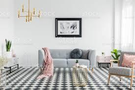 rosa decke und kissen auf graue im weißen wohnzimmer interieur mit poster und sessel echtes foto stockfoto und mehr bilder boden