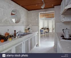 Circular Internal Window Above Sink In Modern Galley Kitchen With White Ceramic Floor Tiles And View Of Dining Room