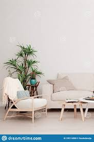 die wand ist mit beigefarbenem sofa zwei tischen und einem