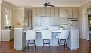 A Ceiling Fan Hangs Over Gray Kitchen Island With End Cabinets Topped White Marble Lined Leather Barstools