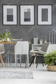 graue stühle die einen holztisch im esszimmer mit den monochromen plakaten stehen die an einer strukturierten wand hängen