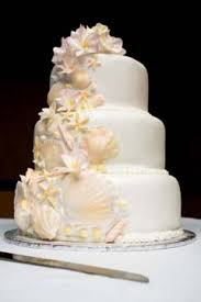 Three Tier White Seashell Cake Perfect For A Beach Theme Wedding Decorated With Seashells And Tropical Floral Topper