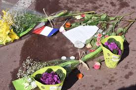 Flowers Candles A French Flag And Note Surround Bloodstain On The Road