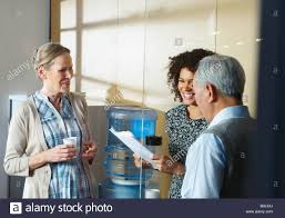 Casual meeting by office water cooler Stock Royalty Free