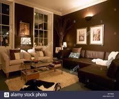 ein modernes braunes wohnzimmer mit sofa sesseln