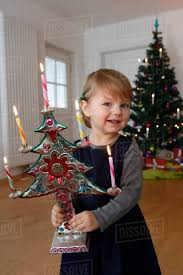 Girl In Front Of Christmas Tree Holding Ornament Looking At Camera Smiling