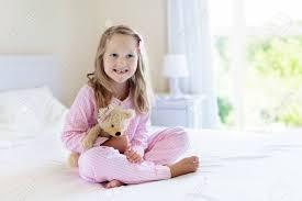 kinder spielen im bett der eltern kinder wachen im sonnigen weißen schlafzimmer auf kleines mädchen in rosa pyjamas nachtwäsche und bettwäsche für
