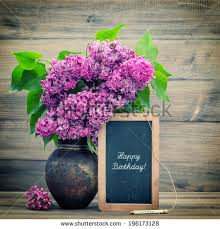 bouquet of lilac flowers on wooden background blackboard with sample text Happy Birthday retro