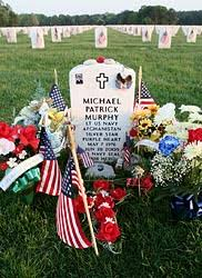 memorial day graveside decorations flowers flags decorate grave of soldier in new york cemetery