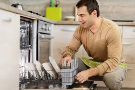 Mid Adult Man Using Dishwasher In The Kitchen