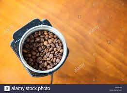 Mocha Coffee Beans Poured Onto An Electric Grinder Ready For Grinding With Copy Space Top View