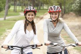 Two Female Friends Riding Bikes In Park Stock Photo Picture And