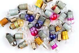 small colored light bulbs on a white background stock photo