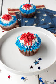 A Red Velvet Cupcake On White Plate With And Blue Frosting