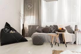 kleine und gemütliche zimmer mit grauen vorhängen einem sofa und teppich
