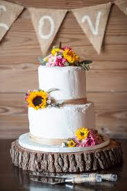 A Two Tier Buttercream Wedding Cake Was Decorated With Raffia Ribbon And Rustic Blooms