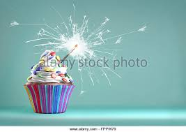 Delicious cupcake with a glittering sparkler and smarties on a whipped cream Colored disks background