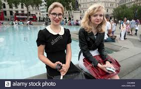 Teenage Girls In Retro Vintage Clothing Sitting By The Fountain Summer Trafalgar Square London England KATHY DEWITT