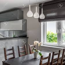 Dining Area With Table, Wooden Chairs And Decorative Window Roller..