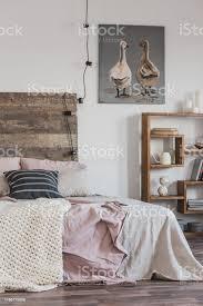 echtes foto einem hellen rustikalen schlafzimmer interieur mit rosa bett holzmöbeln und malerei zwei enten stockfoto und mehr bilder bett