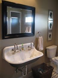 small black white trough sink two faucets under framed mirror