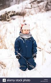 Portrait Of Cute Little Funny Child In Blue Winter Thermal Upper Clothes Playing With Snow