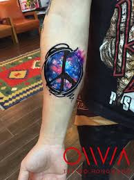 Watercolor Style Galactic Peace Symbol Tattoo On The Right Inner Forearm