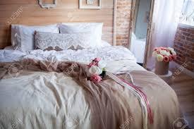 das schlafzimmer ist in der mitte der provence holzwand mit bilderrahmen bedeckt blumenstrauß ist auf dem bett liegend