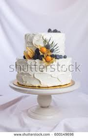 Two Tiered White Cream Cake Decorated With Berries In A Rustic Style Trends For