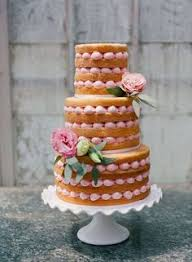 A Naked Wedding Cake With Pale Pink Accents And Real Flowers Perfect For Rustic