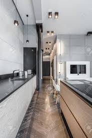 funktionelle küche mit schwarzer arbeitsplatte und deckenleuchten