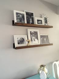 Living Room Floating Brown Wooden Shelves With Picture Frame On It Placed The White