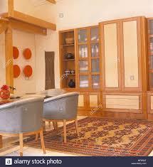 wohnzimmer detail weiße wände holz glas vitrinen leder grau