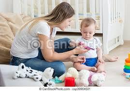 hübsches baby das mit mutter im wohnzimmer auf dem boden