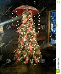 Colorfully Decorated Christmas Tree With Umbrella And String Lights Hanging From The Top