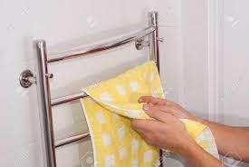 mann hängt ein handtuch auf dem trockner im badezimmer